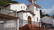Puertas de madera, aleros y paredes blancas, en una arquitectura armónica con el entorno.