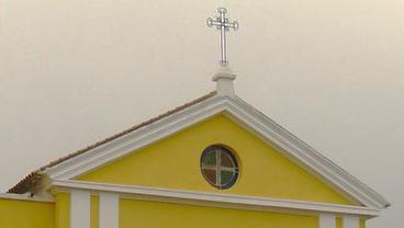 Frontón triangular con ventana circular, óculo y cruz.