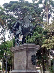 Cartel de protesta en la estatua del Libertador en la plaza Bolívar de Barquisimeto. Patrimonio cultural y crisis política venezolana.